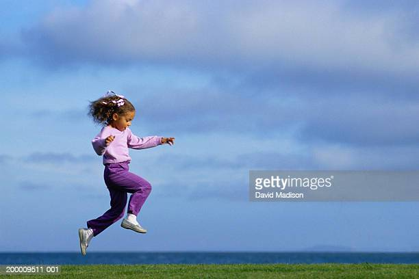 girl (4-6) skipping across grass, profile - skipping along stock photos and pictures