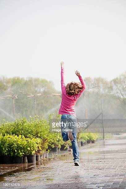 girl skipping along path in plant nursery - skipping along stock pictures, royalty-free photos & images