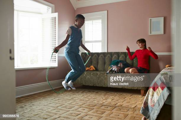 Girl skipping at home, while friend is cheering