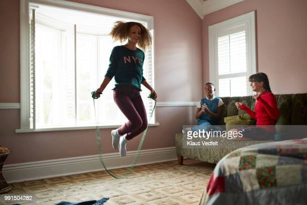 Girl skipping at home, while friends are cheering