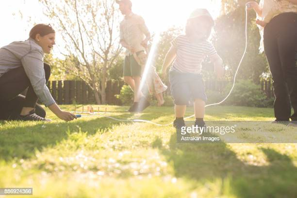 girl (2-3) skipping rope in garden - skipping along stock photos and pictures