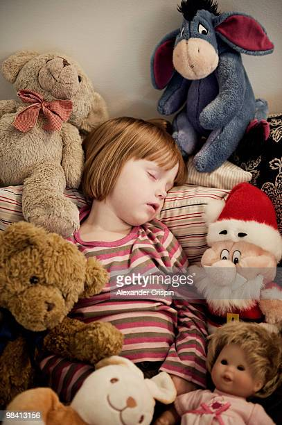 girl sleeping among cuddly toys sweden. - large group of objects stock pictures, royalty-free photos & images
