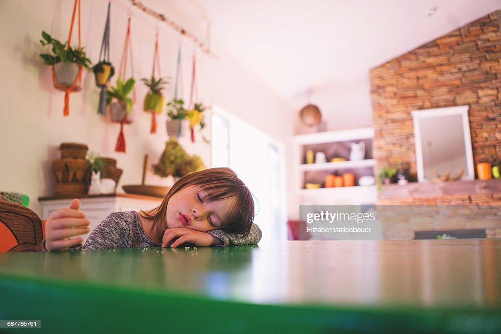 Girl sleeping at kitchen table : Stock Photo