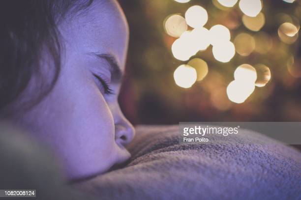 girl sleeping by the christmas tree. - santa face stock pictures, royalty-free photos & images