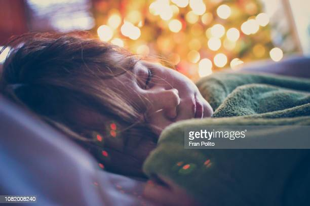 girl sleeping by the christmas tree. - santa face stockfoto's en -beelden