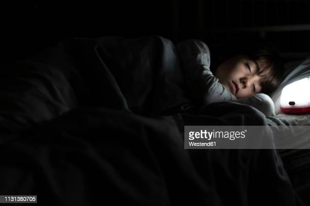 girl sleeping in bed at night with night light - dormir imagens e fotografias de stock