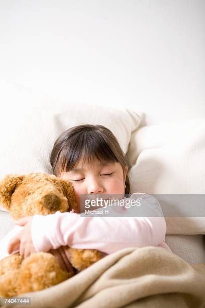 Girl (6-7) sleeping in bed, hugging teddy bear