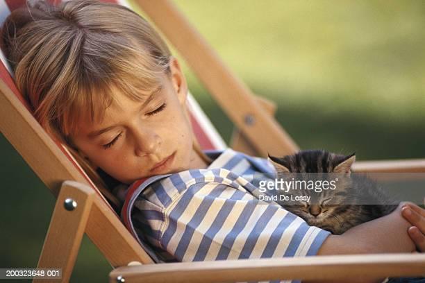 Girl (4-5) sleeping in chair, holding kitten