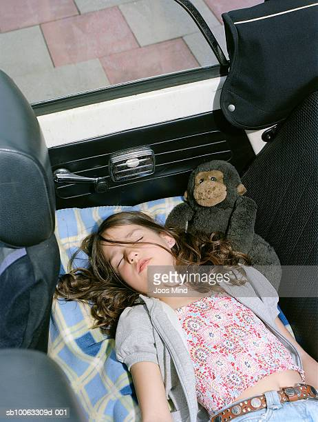 Girl (6-7) sleeping in convertible car, elevated view