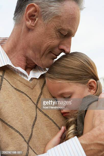 Girl (5-7 years) sleeping in grandfather's arms, close-up