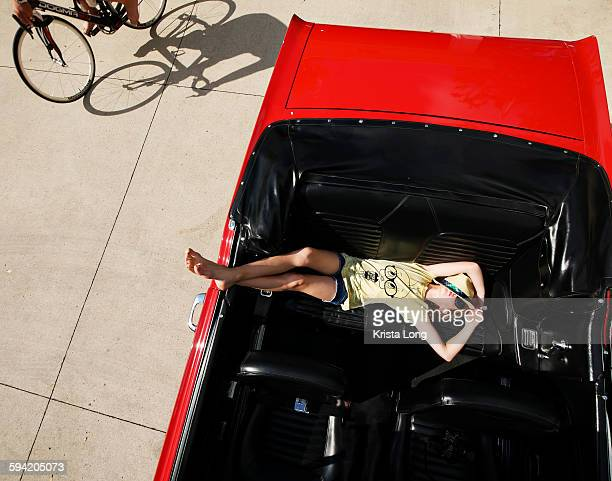 Girl sleeping in the backseat of a car.