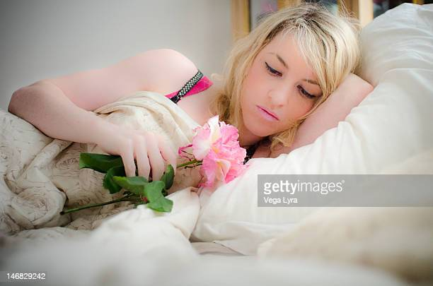 girl sleeping on bed and having flowers in hands - lyra stock photos and pictures