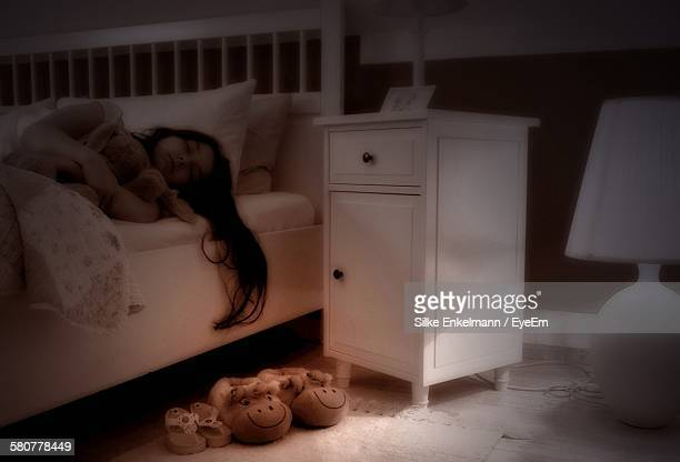 Girl Sleeping On Bed By Illuminated Electric Lamp