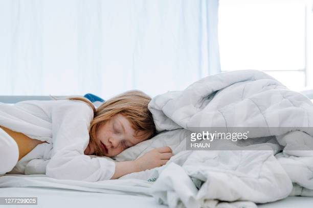 girl sleeping on bed in hospital ward - appendicitis stock pictures, royalty-free photos & images