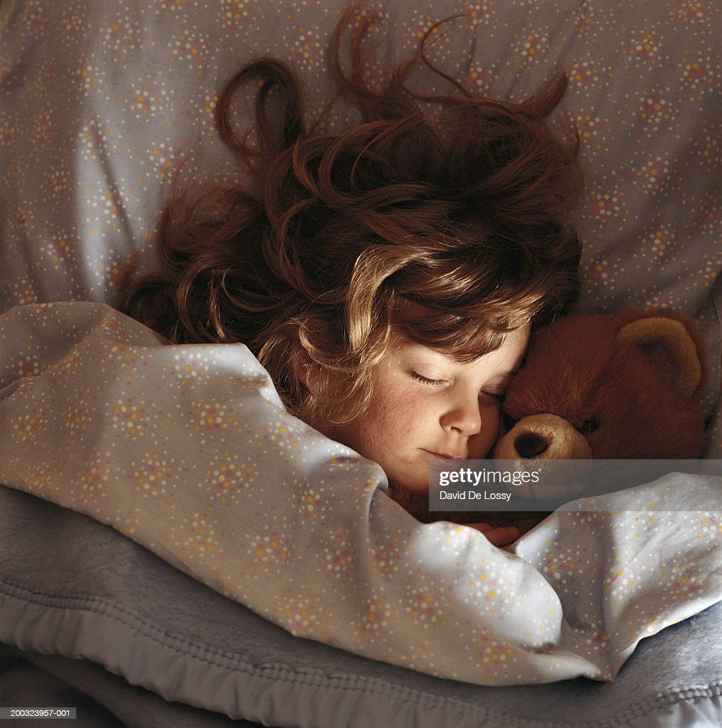 Girl (6-7) sleeping on bed with teddy bear, elevated view : Stock Photo