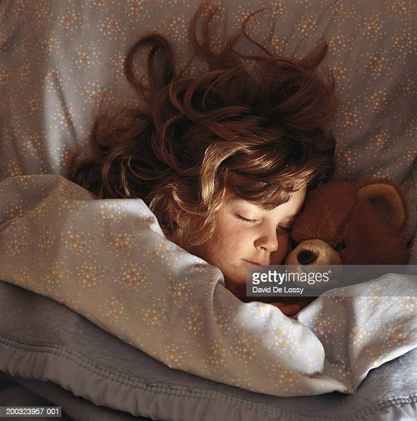 Girl (6-7) sleeping on bed with teddy bear, elevated view