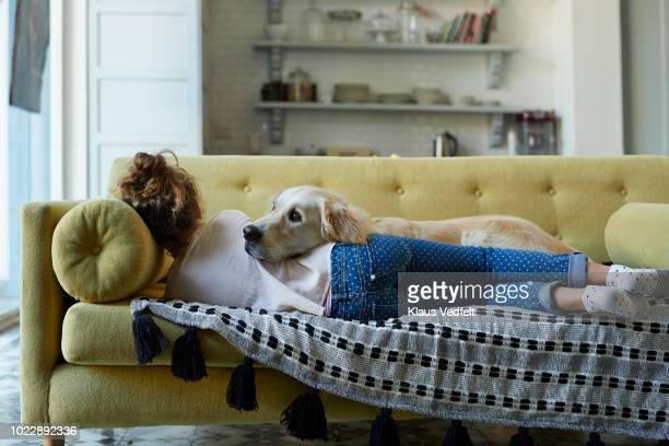 girl sleeping on couch with her golden retriever dog - kindertijd stockfoto's en -beelden