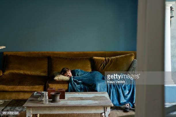 girl sleeping on couch, wrapped in blue blanket - een dutje doen stockfoto's en -beelden