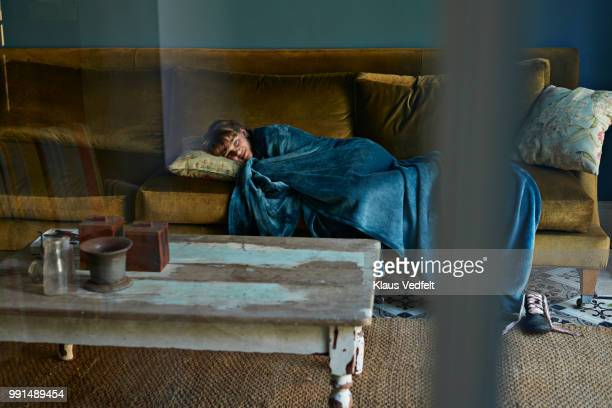 Girl sleeping on couch, wrapped in blue blanket