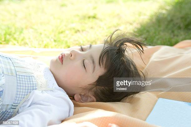 Girl (8-9) sleeping on mat