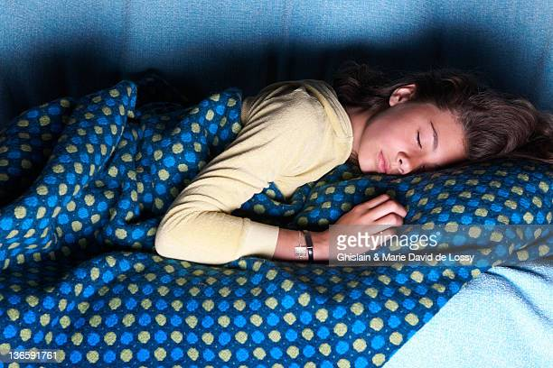 Girl sleeping on sofa with television