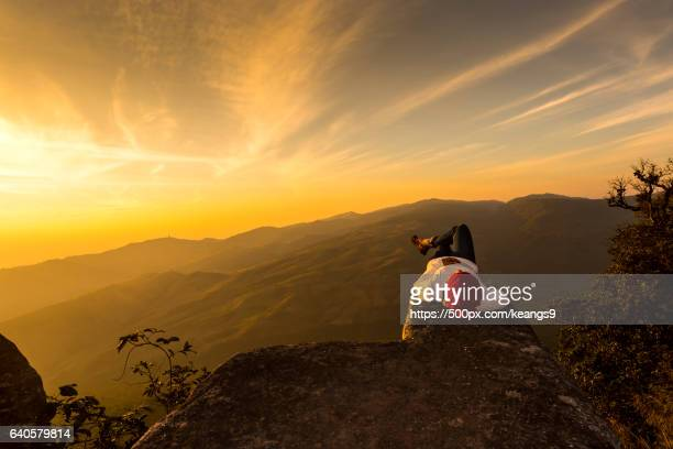 girl sleeping on the rocks at sunrise