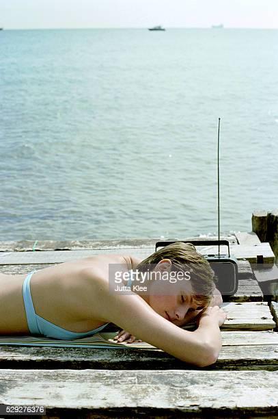 Girl Sleeping on Wooden Jetty