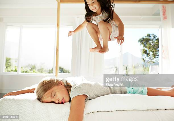 Girl sleeping, while sister jumping in bed