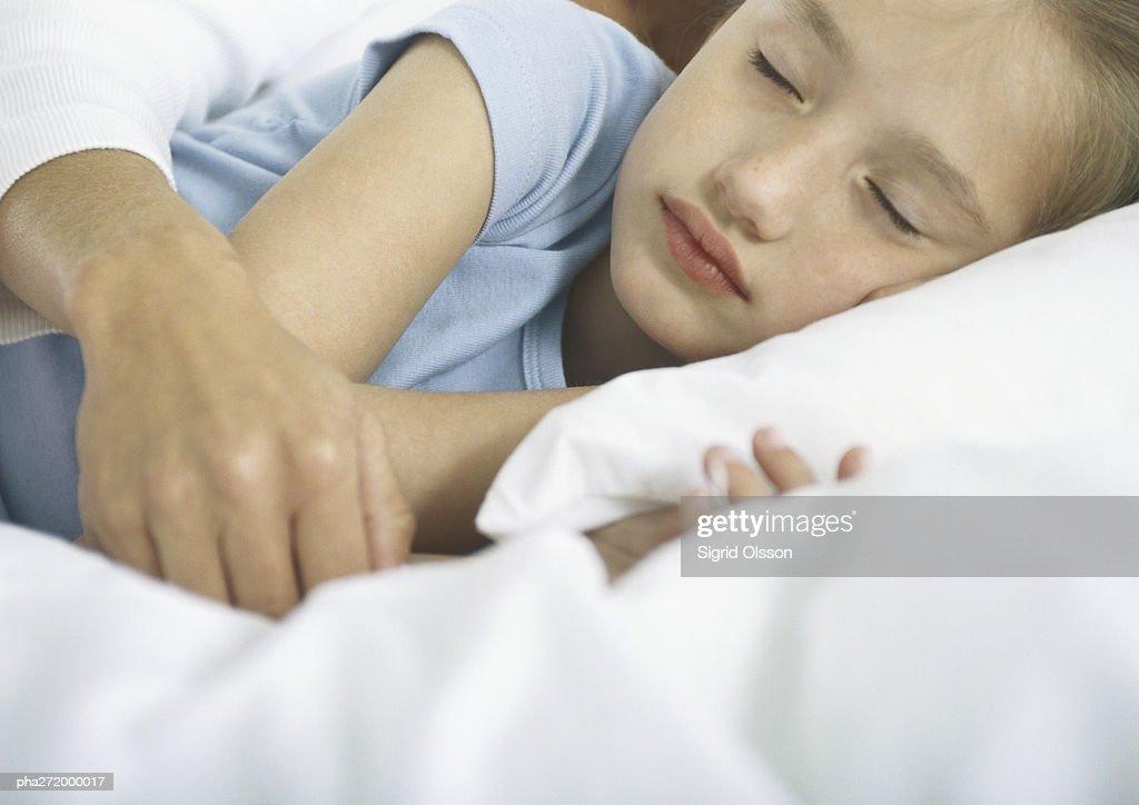 Girl sleeping with woman's arm over her : Stockfoto