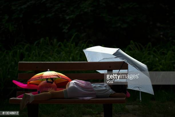 A girl sleeps under umbrellas on a bench on July 12 2017 in Beijing China The dog days of summer start from July 12 in China