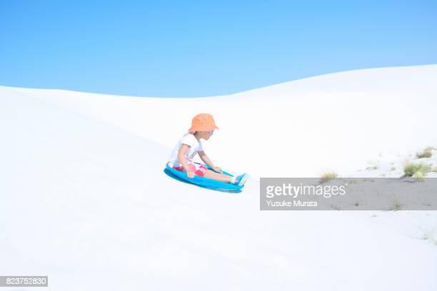 Girl sliding down sand dune