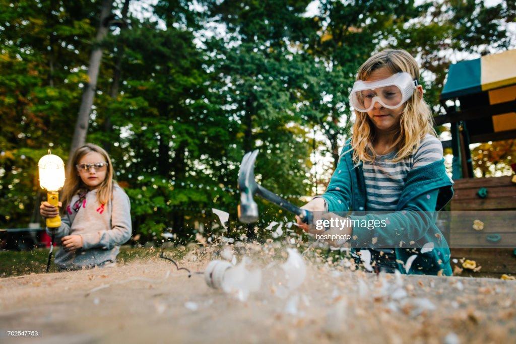 Girl smashing lightbulb with hammer on garden table at dusk : Stock Photo