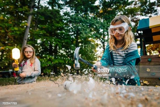 girl smashing lightbulb with hammer on garden table at dusk - heshphoto stock pictures, royalty-free photos & images