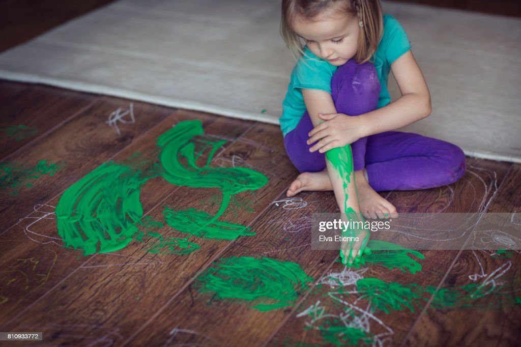 Girl (4-5) smearing green paint on herself and living room floor : Stock Photo