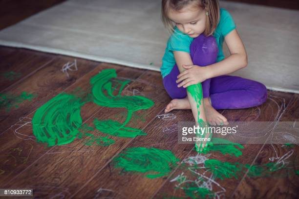 Girl (4-5) smearing green paint on herself and living room floor
