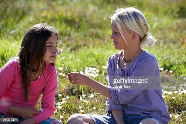 Girl smelling flower in Spring meadow