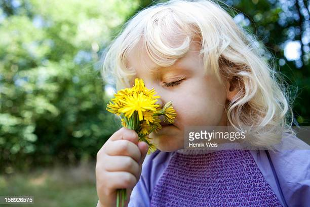 Girl smelling wildflowers outdoors