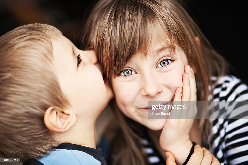 Girl smiles as little brother whispers in her ear : Stock Photo