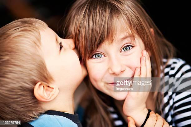 """Mädchen lächelt als kleine Bruder """"whispers in Ihrem Ohr"""