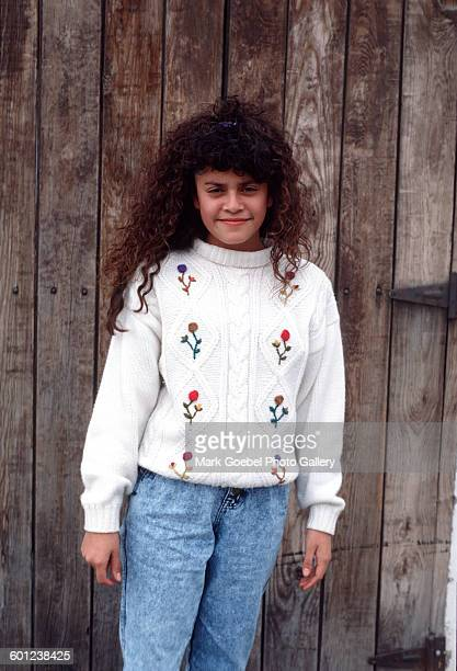 A girl smiles as she stands in front of a brown wooden wall Juarez Mexico late 1980s She wears a white printed sweater and blue jeans