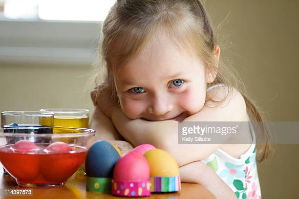 Girl smiles while decorating Easter eggs