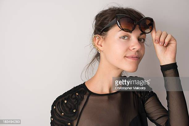 Girl smiles while lifting sunglasses