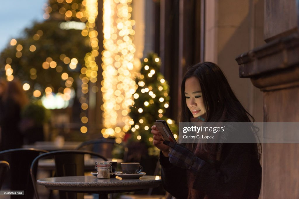 Girl smiles while texting family on her phone - Outdoor Christmas : Stock Photo