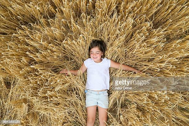 Girl smiling and laying on wheat field