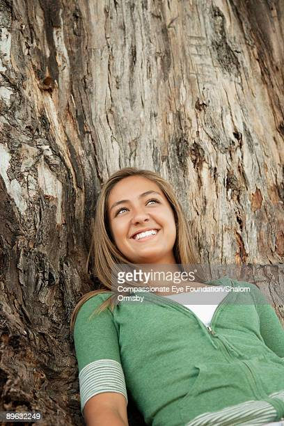 girl smiling and leaning against a tree