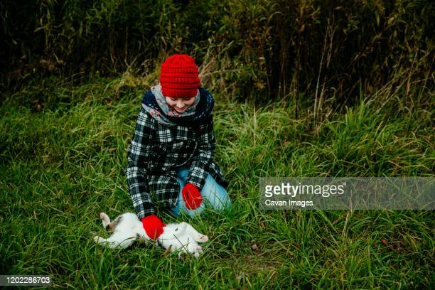 girl smiling as she pets her cats stomach outdoors in the grass - cat with red hat stock pictures, royalty-free photos & images
