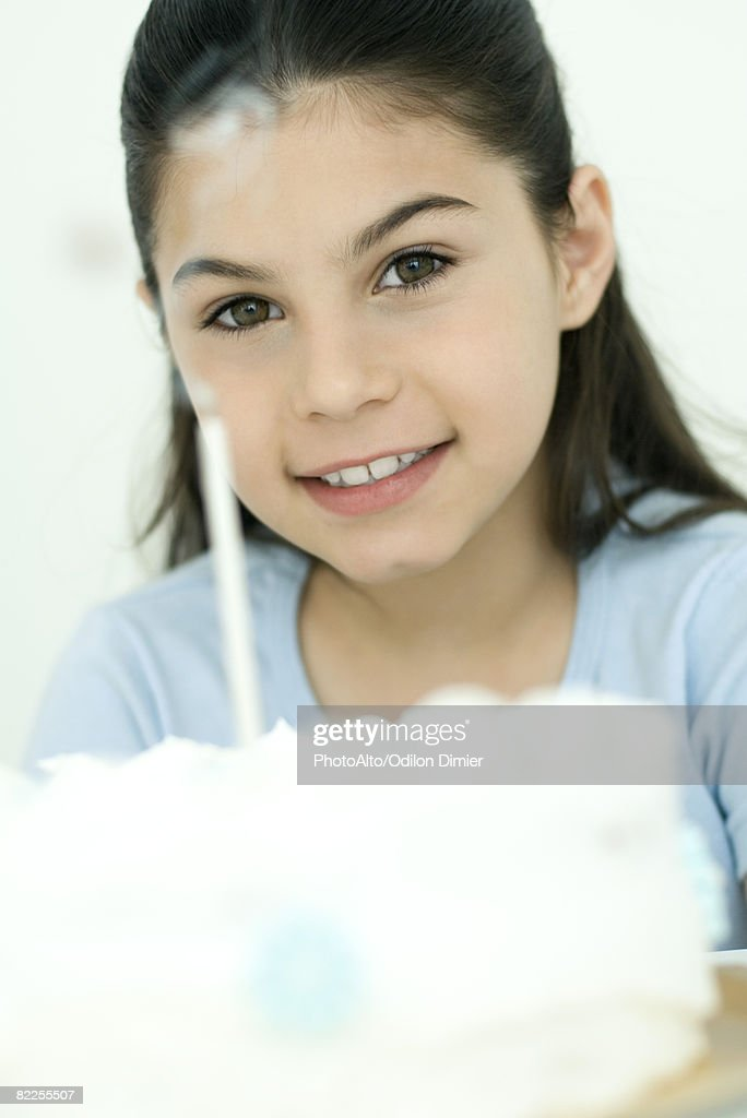 Girl smiling at camera after blowing out candle on birthday cake, portrait : Stock Photo