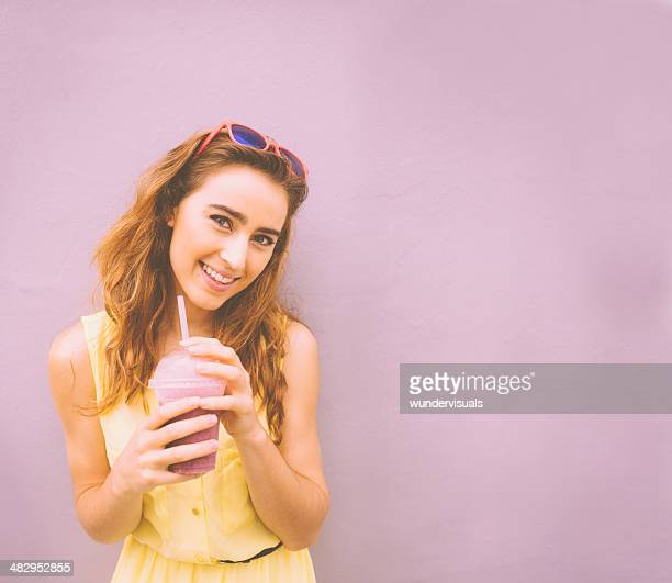 Girl smiling at camera with smoothie