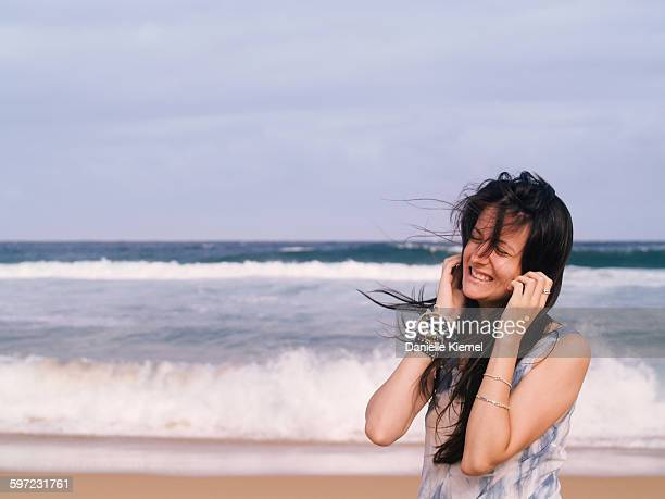 Girl smiling on beach, wind in hair, front view
