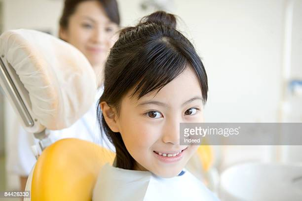 Girl smiling on dentist chair, side view